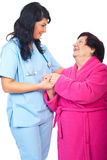 Medico preoccupantesi che tiene le mani anziane della donna Immagini Stock