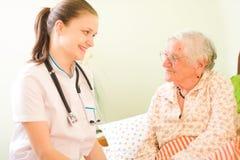 Medico preoccupantesi con la donna anziana ammalata Immagini Stock