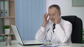 Medico principale stanco dopo avere esaurito giorno lavorativo ed il rilassamento nel suo ufficio video d archivio
