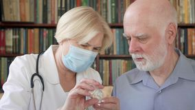 Medico professionista femminile sul lavoro Pillola dante paziente maschio senior di influenza della donna dell'ossequio senior de video d archivio