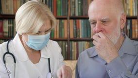 Medico professionista femminile sul lavoro Pillola dante paziente maschio senior di influenza della donna dell'ossequio senior de stock footage