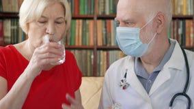 Medico professionista maschio sul lavoro Pillola dante paziente femminile senior di influenza dell'ossequio del medico dell'uomo  stock footage