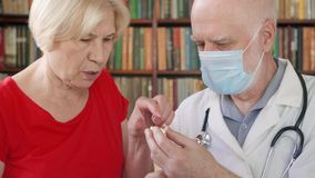Medico professionista maschio sul lavoro Pillola dante paziente femminile senior di influenza dell'ossequio del medico dell'uomo  archivi video