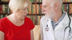Medico professionista maschio sul lavoro Medico senior che consulta paziente malato a casa circa il trattamento stock footage