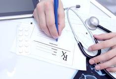 Medico scrive una prescrizione al suo scrittorio Fotografia Stock Libera da Diritti