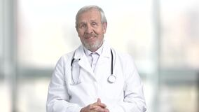 Medico senior allegro che parla con macchina fotografica video d archivio