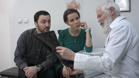 Medico senior maschio che mostra ad una coppia i raggi x in un ufficio stock footage