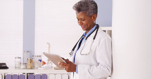Medico senior nero felice che sta nell'ufficio con la compressa Fotografia Stock