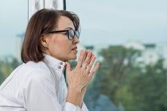 Medico serio della donna nel profilo prega, finestra del fondo immagini stock libere da diritti