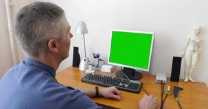 Medico si siede al computer con uno schermo verde stock footage