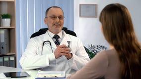 Medico soddisfatto con il risultato di trattamento che parla con paziente femminile, recupero immagini stock libere da diritti