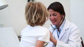 Medico sorridente che auscultating un bambino stock footage