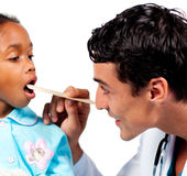 Medico sorridente che controlla la gola della bambina Immagini Stock Libere da Diritti