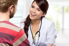 Medico sorridente che dà una consultazione ad un paziente in lei medica Immagine Stock