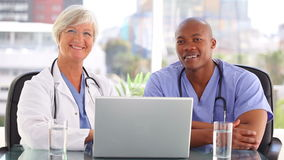 Medico sorridente che parla con un infermiere davanti ad un computer portatile video d archivio