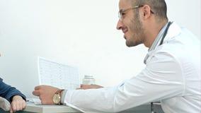 Medico sorridente che spiega i risultati di sistemi diagnostici al suo paziente immagine stock