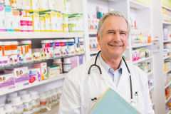 Medico sorridente con i taccuini della tenuta dello stetoscopio Fotografie Stock Libere da Diritti