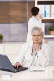 Medico sorridente con l'assistente Immagini Stock