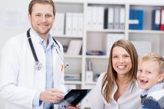 Medico sorridente con una madre e un giovane ragazzo sveglio Fotografie Stock