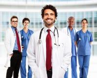Medico sorridente davanti al suo gruppo Fotografie Stock Libere da Diritti
