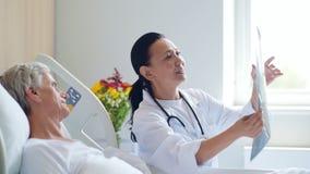 Medico sorridente della donna che discute ricerca del raggio di x con il suo paziente invecchiato stock footage