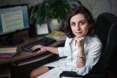 Medico sorridente della giovane donna in un abito medico bianco che si siede ad una tavola Sui libri di tavola, su un monitor del Fotografia Stock