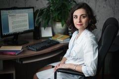 Medico sorridente della giovane donna in un abito medico bianco che si siede ad una tavola Sui libri di tavola, su un monitor del Immagini Stock