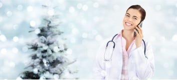 Medico sorridente di Natale con lo Smart Phone sulle luci vaghe con fotografie stock libere da diritti