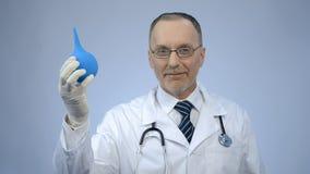 Medico sorriso felice di proctologia che mostra siringa di gomma e che esamina macchina fotografica Immagine Stock