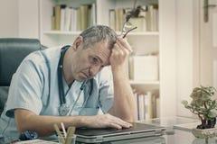 Medico sovraccarico nel suo ufficio Immagine Stock