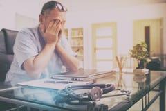 Medico sovraccarico nel suo ufficio Fotografie Stock