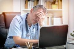 Medico sovraccarico nel suo ufficio Fotografia Stock Libera da Diritti