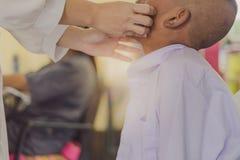 Medico sta controllando la cavità orale di uno studente fotografie stock