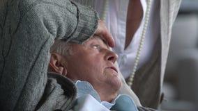 Medico sta parlando con uomo anziano malato e sua moglie archivi video