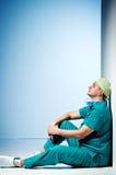 Medico stanco si siede sul pavimento nel corridoio dell'ospedale fotografie stock libere da diritti