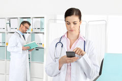 Medico sul telefono, con il collega in ufficio medico fotografia stock