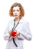 Medico sveglio della testarossa in cappotto del laboratorio con cuore Immagine Stock Libera da Diritti