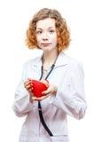 Medico sveglio della testarossa in cappotto del laboratorio con cuore Immagini Stock Libere da Diritti