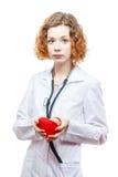 Medico sveglio della testarossa in cappotto del laboratorio con cuore Fotografie Stock
