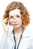 Medico sveglio della testarossa in cappotto del laboratorio con i vetri Immagine Stock Libera da Diritti