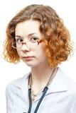 Medico sveglio della testarossa in cappotto del laboratorio con i vetri Fotografie Stock Libere da Diritti