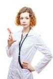 Medico sveglio della testarossa in cappotto del laboratorio con la siringa Fotografie Stock Libere da Diritti