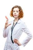 Medico sveglio della testarossa in cappotto del laboratorio con la siringa Fotografia Stock