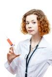 Medico sveglio della testarossa in cappotto del laboratorio con la siringa Fotografie Stock
