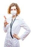 Medico sveglio della testarossa in cappotto del laboratorio con la siringa nella maschera Fotografia Stock Libera da Diritti