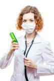 Medico sveglio della testarossa in cappotto del laboratorio con la siringa nella maschera Fotografia Stock