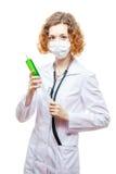 Medico sveglio della testarossa in cappotto del laboratorio con la siringa nella maschera Fotografie Stock Libere da Diritti