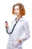 Medico sveglio della testarossa in cappotto del laboratorio con lo stetoscopio Fotografia Stock