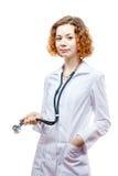 Medico sveglio della testarossa in cappotto del laboratorio con lo stetoscopio Immagini Stock Libere da Diritti