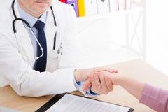 Medico tiene la mano paziente in ufficio Il risultato dell'esame, prova positiva, calma, promette ed incoraggia su Assicurazione- fotografie stock